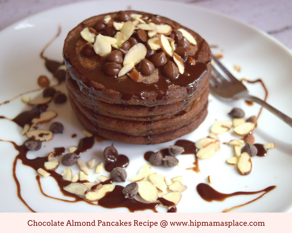 a photo of chocolate almond pancakes stack drizzled with chocolate syrup